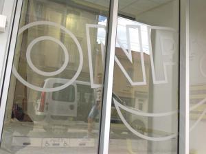 Големи надписи върху стъклена врата от матово фолио